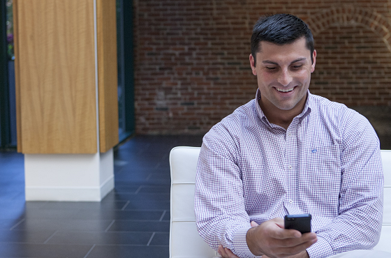 Man Smiling While Looking At His Cell Phone