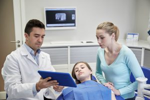 dentist and parent in exam room looking at an ipad as the child lays in the chair